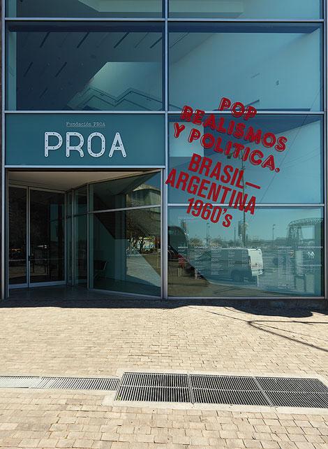 La marca Proa aplicada al vidrio, elemento central de la identidad arquitectónica, junto a gráfica de entorno de la exposición actual.